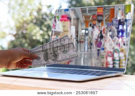 Hand Holding Two One Hundred Dollar Bills Above Laptop Keyboard With Image Of Supermarket On Screen
