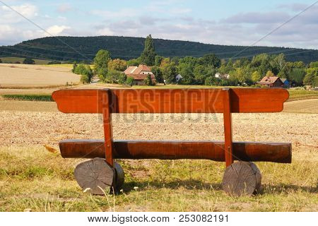 Wooden Bench In Front Of A Wide Summer Landscape With A Village, Fields And Woodland