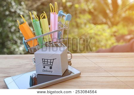 Shopping Bags Are In Trolley And Cardboard Box Is On Smartphone. Consumers Can Buy Products Directly