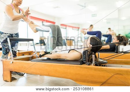 Pilates Instructor Assisting Young Woman On Reformer Machine In Gym