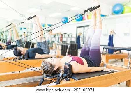 Determined Young Female Pulling Resistance Bands With Legs On Pilates Reformer In Gym
