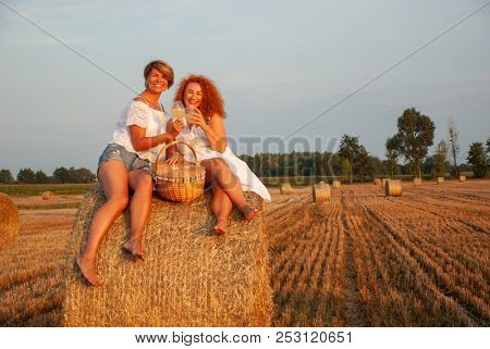 Two attractive women have picnic drink white vine and having fun on a haystack