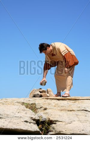 Full length man in brown and beige tunic robe bending over near a pile of rocks. Concept sin law or culture. This form of punishment was used in many ancient cultures and is still used in some cultures today. Space for a heading title or verse. poster