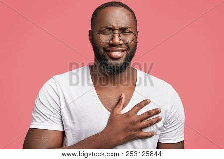 Glad Middle Aged African American Man With Cheerful Expression, Laughs Pleasantly At Funny Anecdote,
