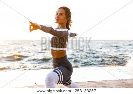 Image of amazing strong young fitness woman outdoors in the beach make yoga stretching exercises.