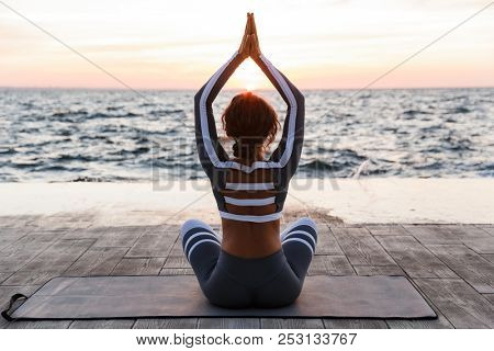Back view photo of strong young fitness woman outdoors in the beach make yoga meditate exercises.