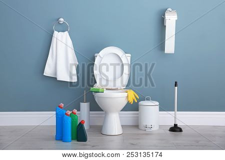 Ceramic Toilet Bowl, Bottles Of Detergent And Cleaning Supplies In Modern Bathroom