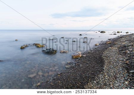 Sea Shore With A Blurred Wave That Rolls On The Shore Through Large Boulders