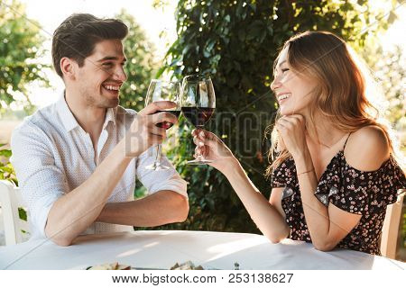 Picture of young loving couple sitting in cafe by dating outdors in park holding glasses of wine drinking.