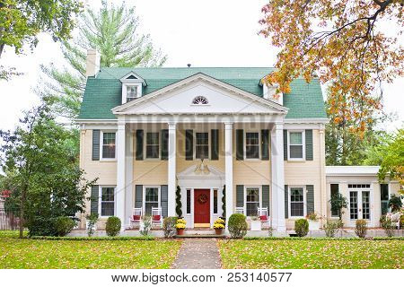 Large White Southern Style Home With A Columns, A Red Door And A Turquoise Roof. The Yard Features A