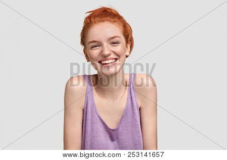 Portrait Of Happy Freckled Female With Ginger Hair, Has Broad Smile, Glad To Meet With Someone, Dres