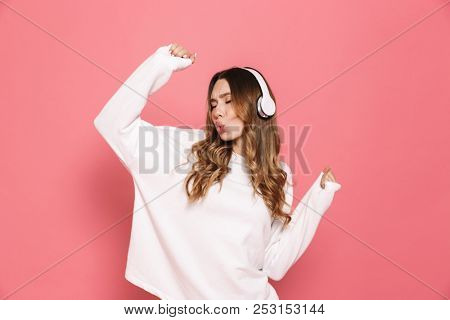 Portrait of a happy young woman in headphones listening to music isolated over pink background, dancing