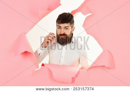 Bearded Man Look Through Paper. View Of Male Face Through Hole In Pink Paper. Man Making Hole In Pap