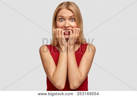 Embarrassed blonde female bites finger nails, looks surprisingly and with worried expression, hears negative news, feels anxious before travelling by plane for first time, dressed in red clothes poster