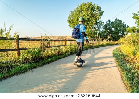 An adult man is riding an electric skateboard on the Poudre River Trail in northern Colorado.It is a  paved bike trail extending more than 20 miles between Timnath and Greeley.