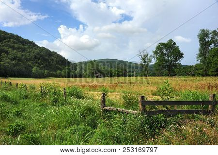 Landscape Image Of Old, Wooden Barn Nestled In A Field With Trees.  Ozark Mountains Rise Around Rust