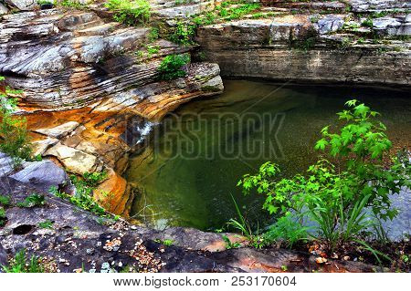 Hidden Pool Has Calm And Still Surface.  Water Trickles In From A Small Cascade On The Rocky Ledges.