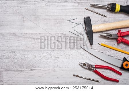 Tool Set Of Hammer, Nails, Screwdriver, Pliers, Pen And A Saw On A Wooden Table - Top Down View With
