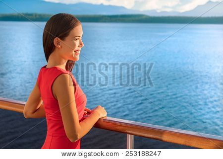 Luxury travel cruise ship elegant Asian woman on Alaska destination cruising holiday. Happy lady looking at sunset view of ocean from boat balcony deck.