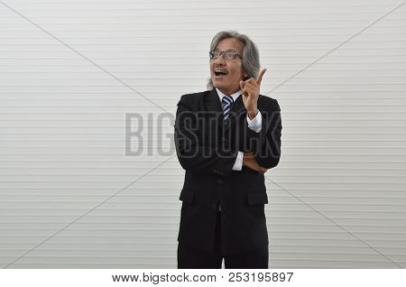Elderly Asian Businessman In Black Suit And Eyeglasses Get New Idea And Pointing Finger Up, Business