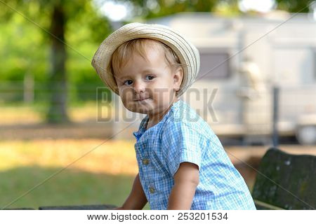 Cute Pensive Trendy Young Baby Boy In A Blue Outfit And Sunhat Sitting Looking Thoughtfully To The S