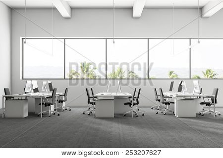 Company Office Interior With A Gray Carpet And Rows Of White Computer Desks. Industrial Style Interi