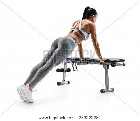 Sporty Woman Doing Push Ups On Sports Bench. Photo Of Fitness Model In Sportswear Isolated On White