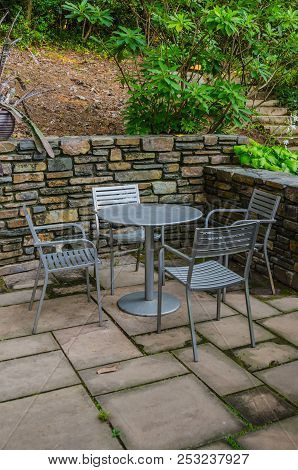 A Table With Four Chairs In An Outdoor Cafe Makes A Cozy Spot To Catch Up Over Lunch Or Coffee