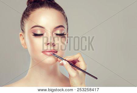 Makeup Artist Applies  Pink Gloss Lipstick  . Beautiful Woman Face. Hand Of Make-up Master, Painting