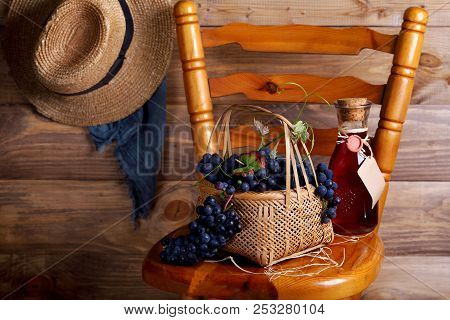 Grapes In A Basket On A Chair With A Bottle Of Wine