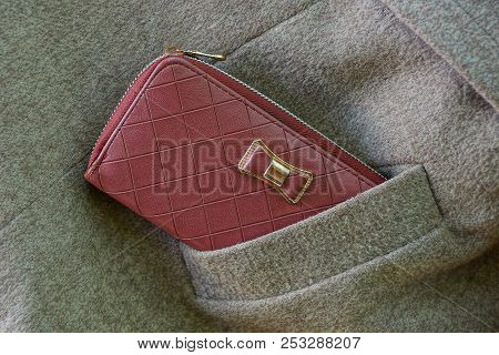 Red Purse In A Gray Pocket Of Woolen Clothes