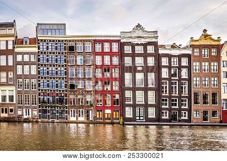 Amsterdam, The Netherlands - Oct. 20, 2014: Row Of Historic Houses Along The Damrak Canal, Dating Ba