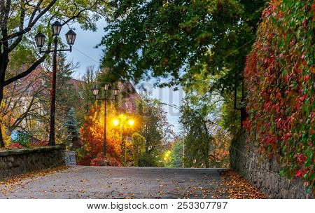 Streets Of Old City At Dawn. Beautiful Autumn Scenery With Red Ivory On Wall And City Lanterns
