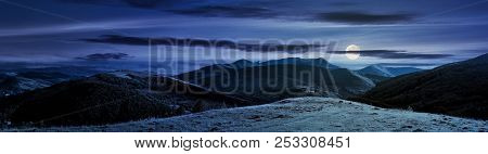 Panorama Of Mountainous Countryside At Night In Full Moon Light. Beautiful Evening Weather With Clou