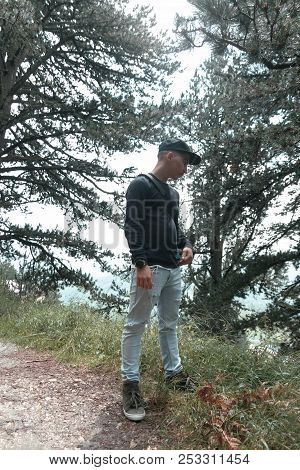 Young Hiker Watching Sideways In Front Of Pine Trees