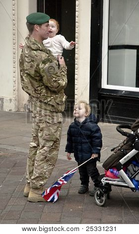Soldier from from 3 Commando Brigade a holds a child