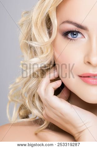 Beauty Portrait Of Attractive Blond Woman With Curly Hair And A Beautiful Hairstyle. Makeup And Cosm