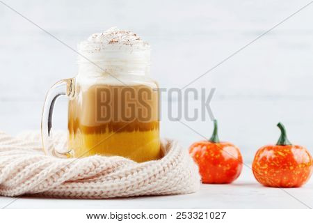 Pumpkin Spiced Latte Or Coffee In Glass Jar Decorated Knitted Scarf On White Table. Autumn, Fall Or
