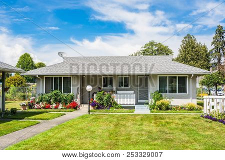 Small residential duplex house with concrete pathway over front yard and blossoming flowers at the entrance poster