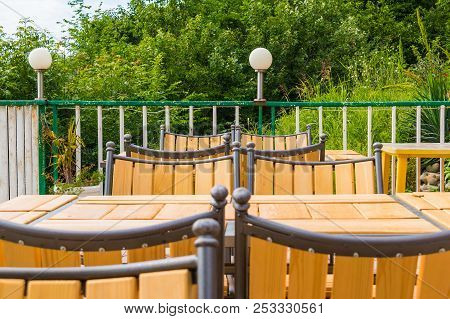 Terrace With Wooden Tables And Chairs On The Background Of Lush Vegetation In Summer Day