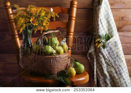 Pears In A Wicker Basket With A Bouquet Of Flowers And A Butterfly