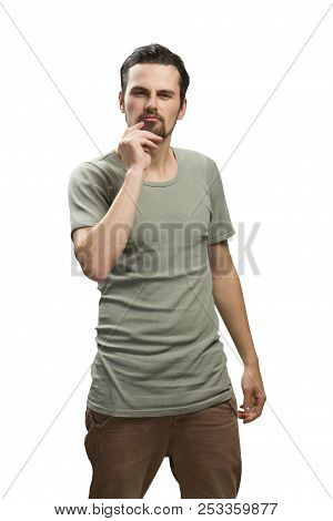 Studio Portrait Of A Good Looking Thinking Young Man. Against White Background With Green T-shirt. N