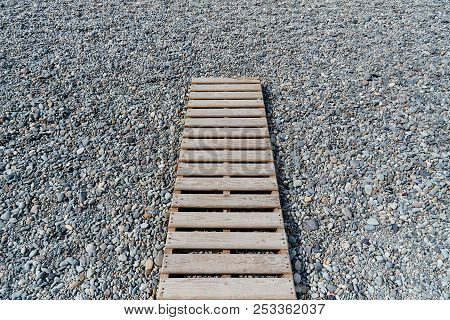 A Wooden Walkway Close-up On A Pebble Beach.