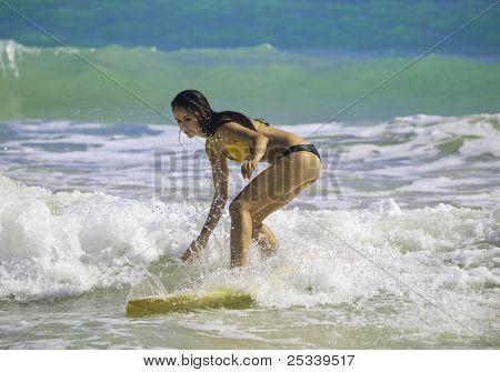 brunette in bikini surfing
