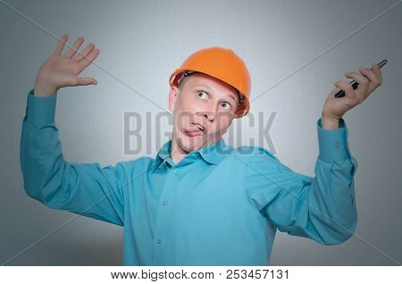 Perplexed crazy builder worker with mobile phone isolated on gray background. poster
