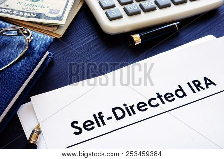 Self-Directed IRA SDIRA documents on a desk. poster