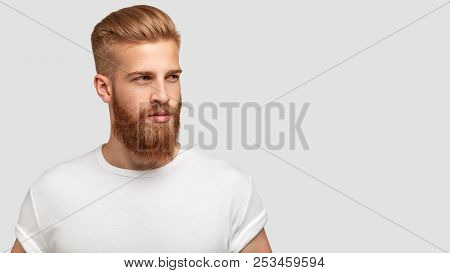 Serious Thoughtful Male With Ginger Beard, Dressed Casually, Focused Somewhere, Isolated Over White