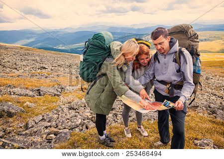 Travel Lifestyle And Survival Concept Rear View. Two  Hiking Women And Man With Backpack Go Along Th