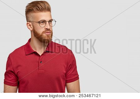 Sideways Shot Of Ginger Male With Trendy Haircut, Thick Beard, Focused Aside, Thinks About New Proje