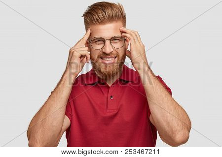 Photo Of Cheerful Red Haired Young Hipster Has Bad Memory, Keeps Hands On Temples, Tries To Remember
